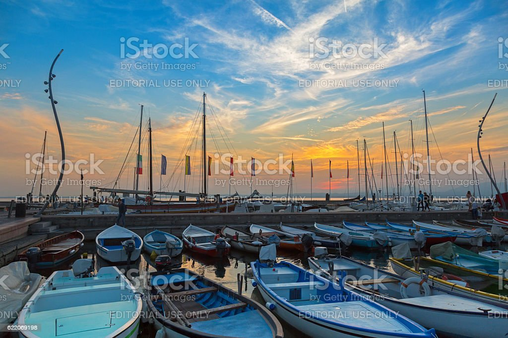 Sailboats fishing boats during sunset at Garda Lake harbor, Italy stock photo