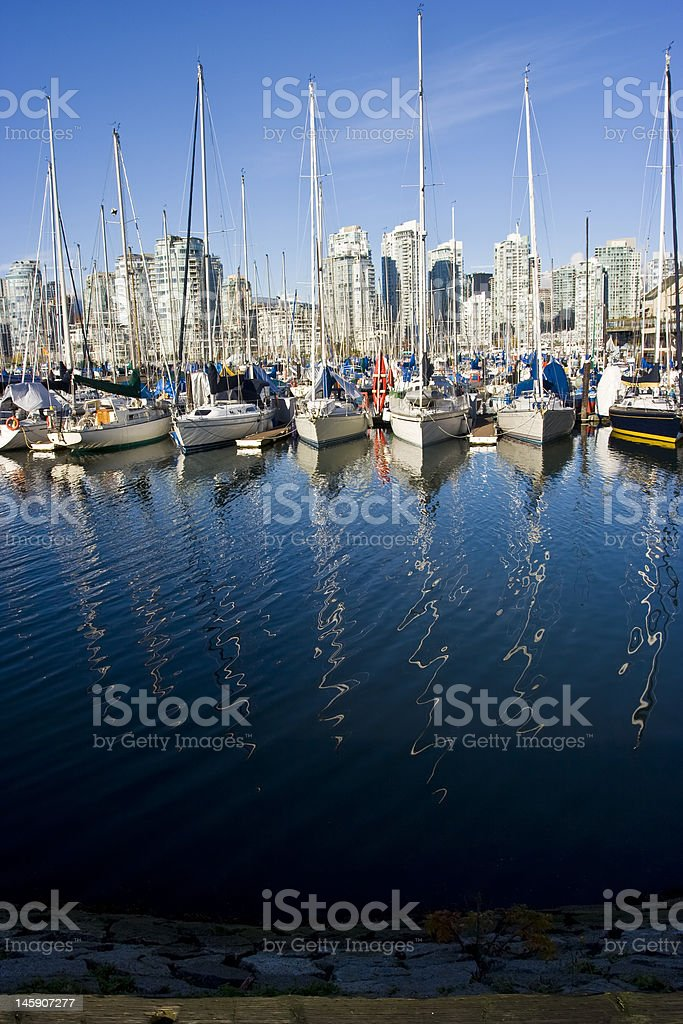 Sailboats in a vancouver marina with mast reflections royalty-free stock photo