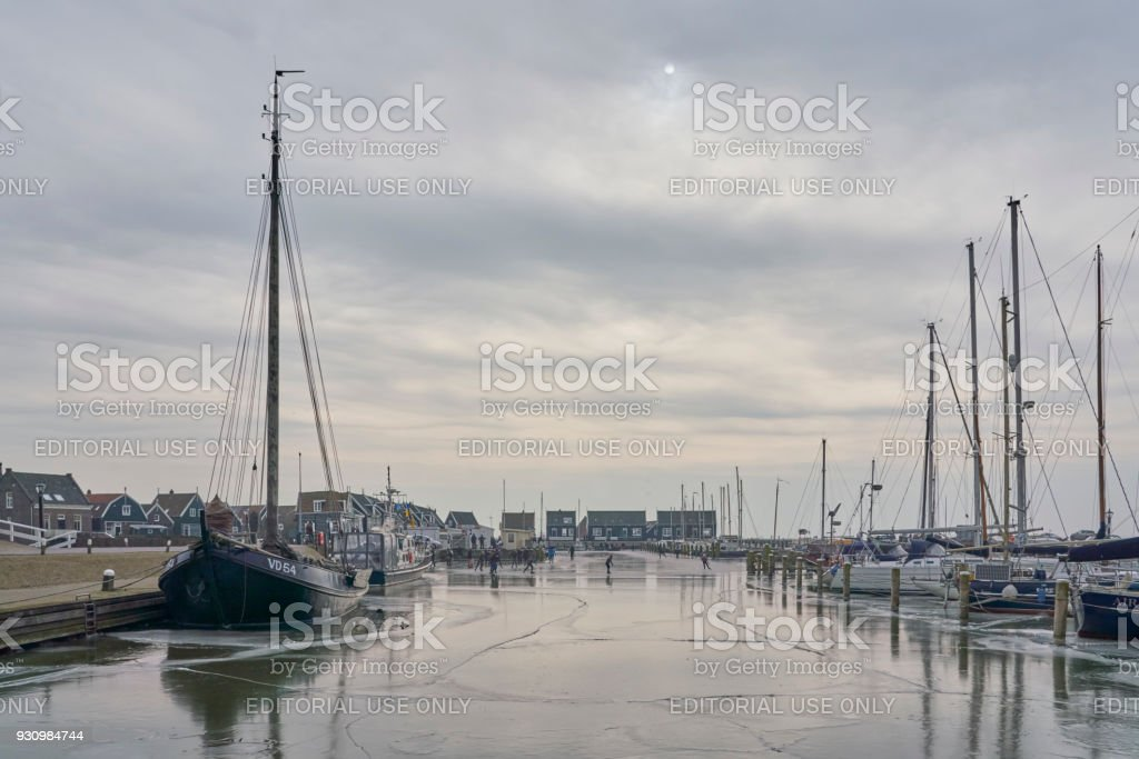 Sailboats In Frozen Harbor Of The Old Island Marken With Dutch Skaters  Enjoying The Chance To Skate Amidst The Green Wooden Houses Stock Photo &  More