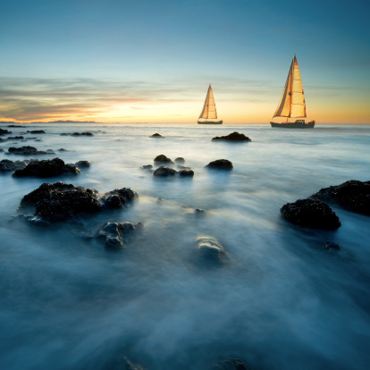 Sailboats On Sea At Dusk Stock Photo - Download Image Now