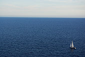 This picture is taken in Santorini island, Greece. 2008 autumn. You can see a lonely sailing ship  swiming towards unknown direction.
