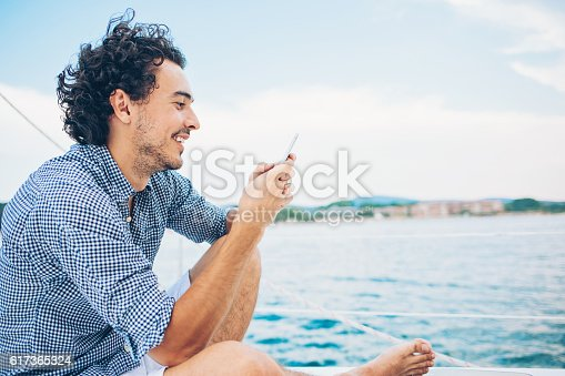 Smiling young man traveling on a yacht in the sea in the summer and text messaging.