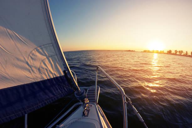 segeln bei sonnenuntergang. ein blick vom deck der yacht zu segeln und bogen. - kalifornien ostsee stock-fotos und bilder