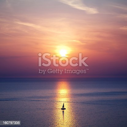 Small sailing boat right in the center of the beautiful sunset.