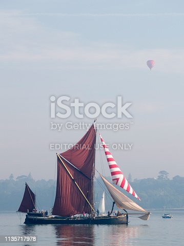 A restored historical sailing barge in the estuary in Suffolk with a hot air balloon passing over head.