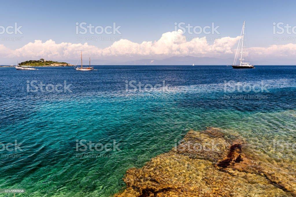 Barco à vela e uma pequena ilha no mar Jônico - foto de acervo