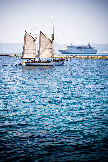 Sailing boat and cruise liner stock photo