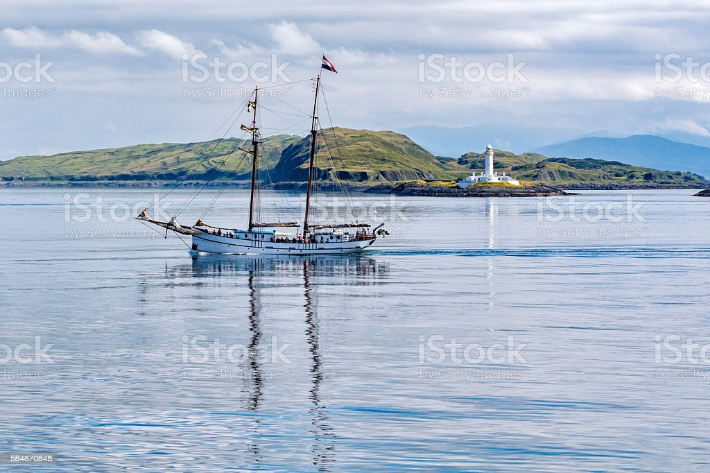 Sailing Boat in front of Eilean Musdile Lighthouse Just off Lismore Island between Oban and Isle of Mull Argyll and Bute Stock Photo