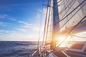 sailing boat in open sea at sunset, beautiful luxurious yacht crossing ocean