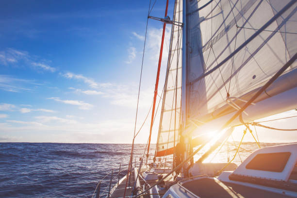sailing boat in open sea at sunset - sail stock pictures, royalty-free photos & images
