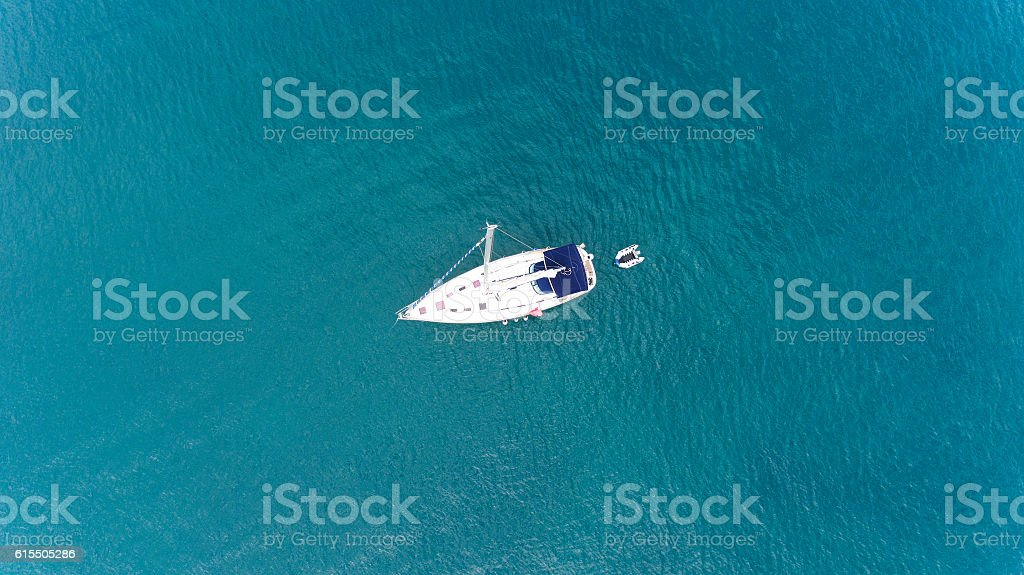 Sailing boat in the middle of turquoise clear sea waters стоковое фото