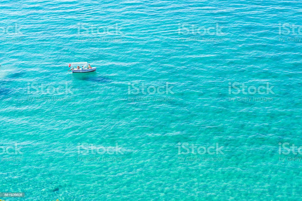 Sailing boat in the middle of turquoise clear sea waters stock photo
