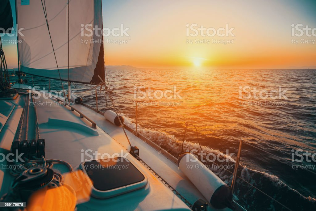 Sailing boat in the sea during awesome sunset. Luxury yacht and cruise holiday. stock photo