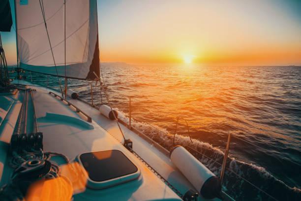 Barco à vela no mar durante o pôr do sol incrível. Iate de luxo e férias de cruzeiro. - foto de acervo