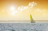 Sailing boat in the sea on the golden sky background