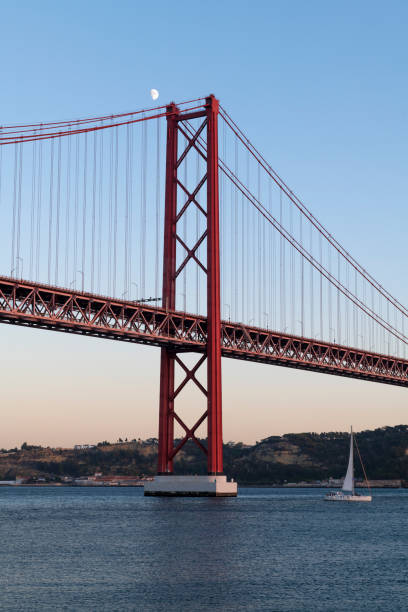 Sailing boat in the Tagus River passing by the 25 of April Bridge (Ponte 25 de Abril), in the city of Lisbon, Portugal stock photo