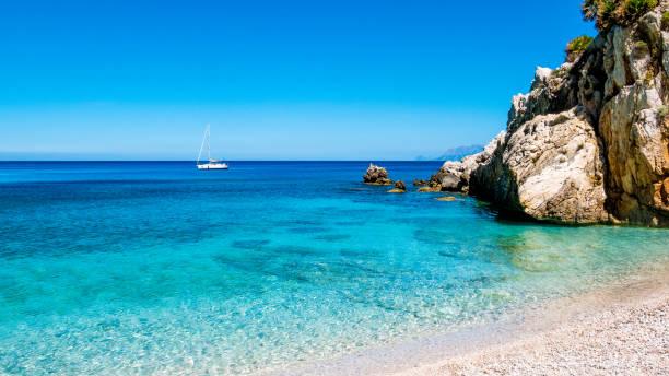 ein segelboot in der türkisblauen mittelmeer, bei san vito lo capo, sizilien, italien. - sizilien strände stock-fotos und bilder