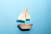 a white sailing boat of the tin plate on blue background like the ocean.