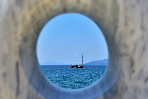 Sailing boat on blue sea on blurred background of mountains and blue sky. View through round hole of granite stone with blurred foreground