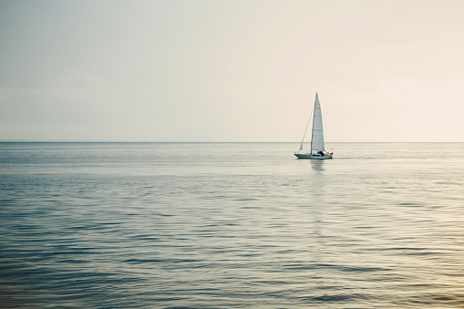Sailing boat on open sea at sunset.