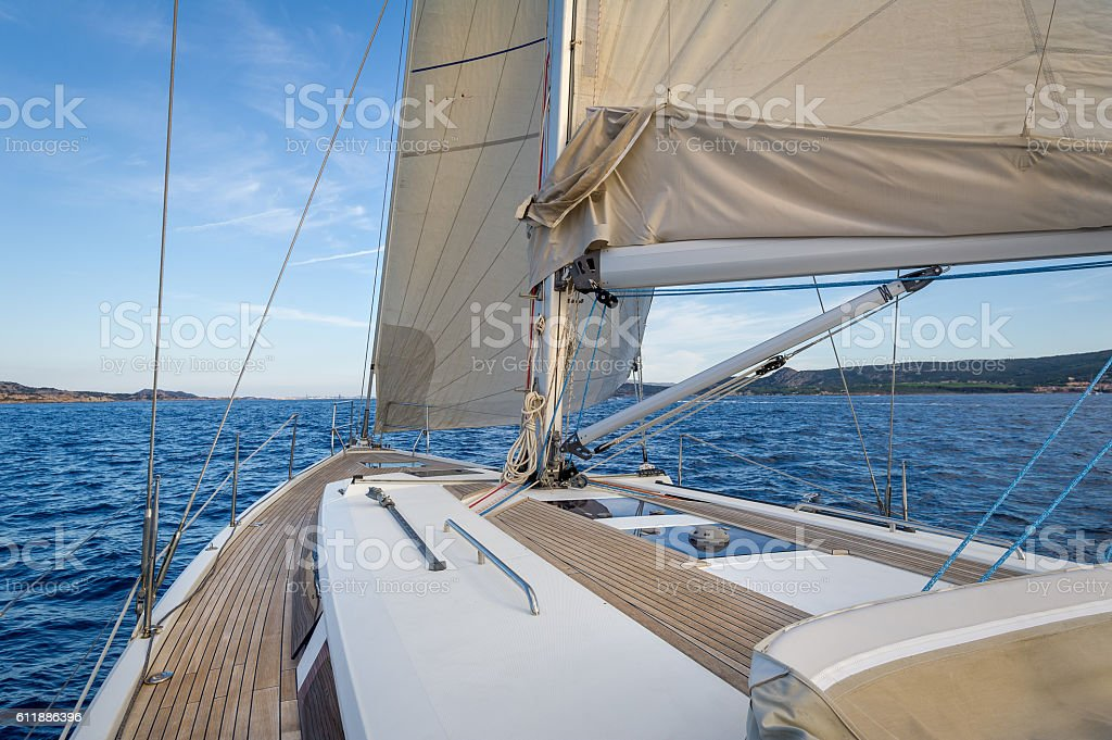 Sailing boat teak deck and hoisted sails, view from the stock photo