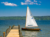 empty sailing boat at a pier on a sunny day near munich, germany