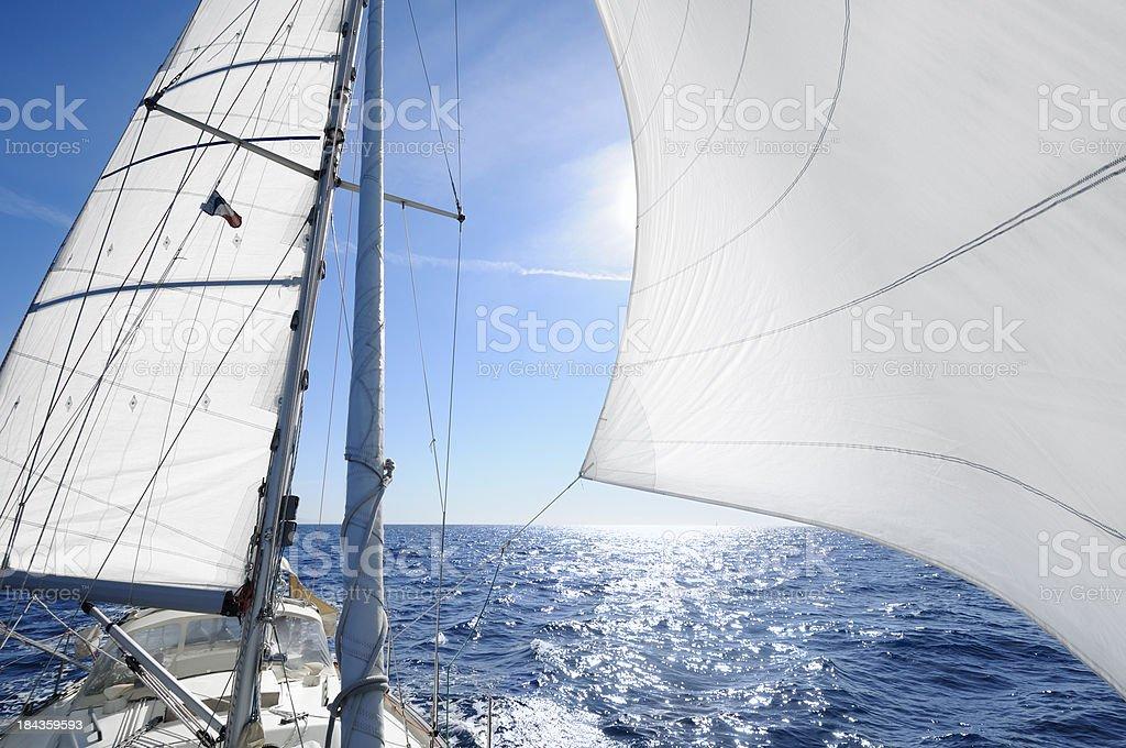 Sailing boat with the sun shingn behing sail stock photo