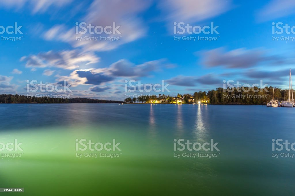Sailing boats and yachts in marina at night with cloudy sky. stock photo