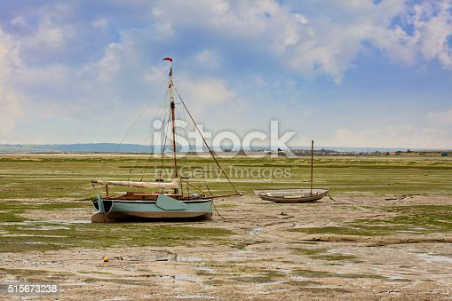 Traditional wooden sailing / fishing boats sitting on the estuary mud flats during low tide.