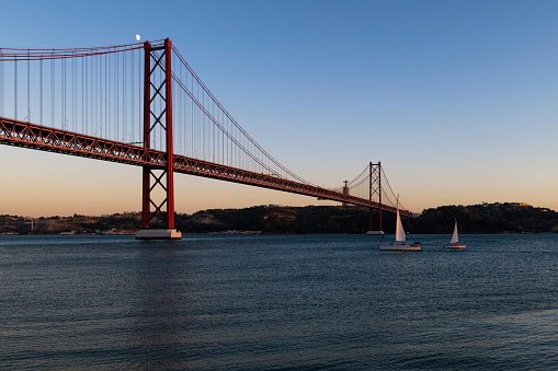 Sailing boats in the Tagus River passing by the 25 of April Bridge (Ponte 25 de Abril), in the city of Lisbon