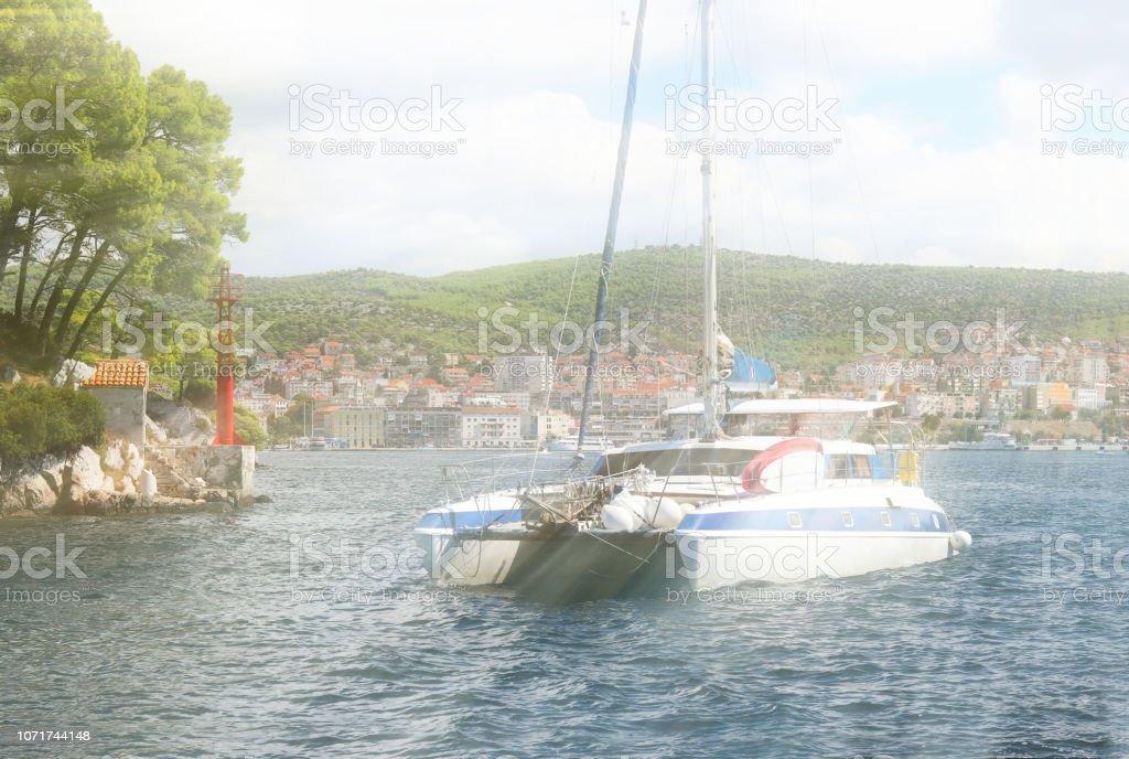 Sailing catamaran sails along the rocky green coast past the red literary sign - the fairway lighthouse. City of Sibenik in the Dalmatia region in Croatia. Adriatic sea in the Mediterranean area.