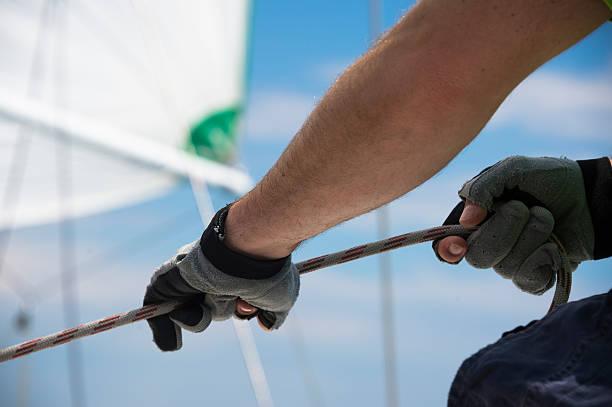 segeln mitglied der besatzung ziehe dabei das seil auf segelboot - segelhandschuhe stock-fotos und bilder
