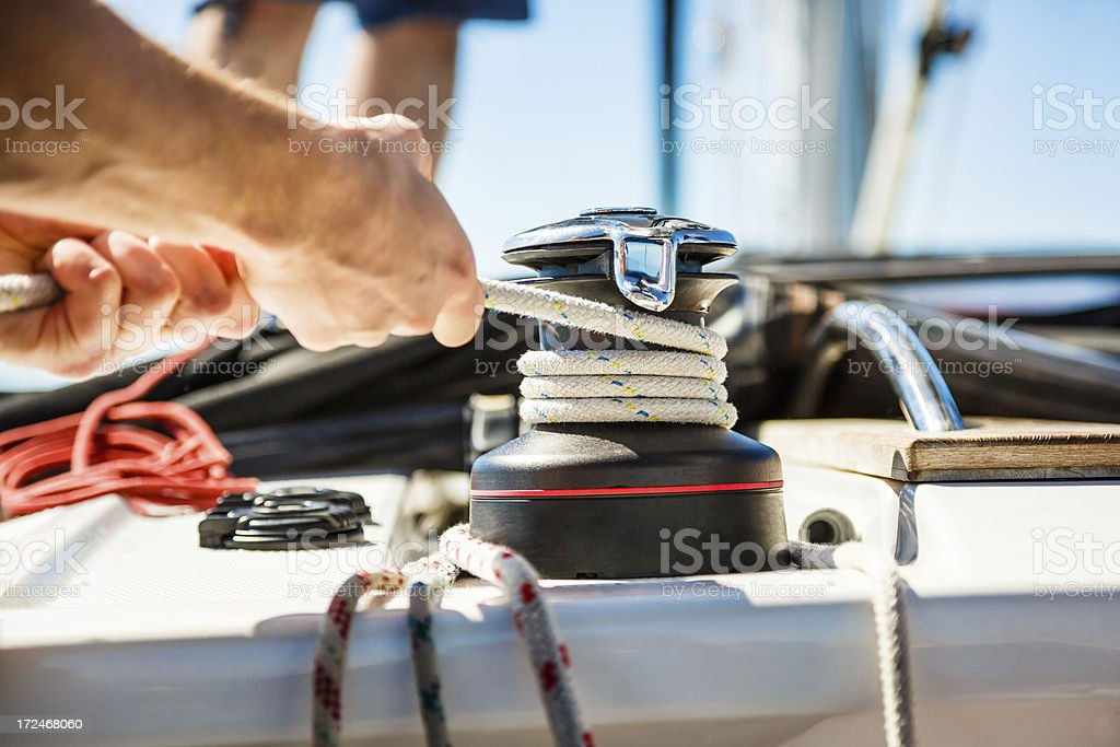 Sailing crew member pulling rope on sailboat stock photo