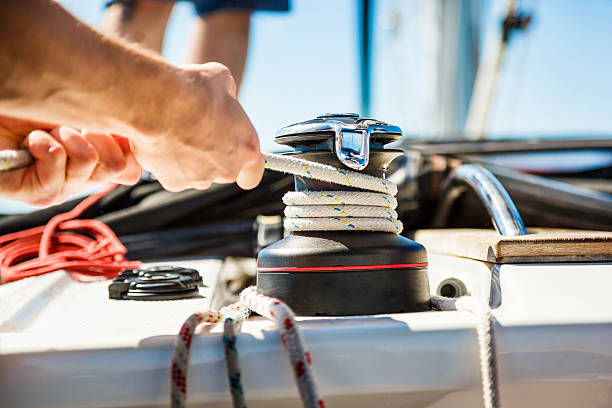 sailing crew member pulling rope on sailboat - cable winch stock photos and pictures