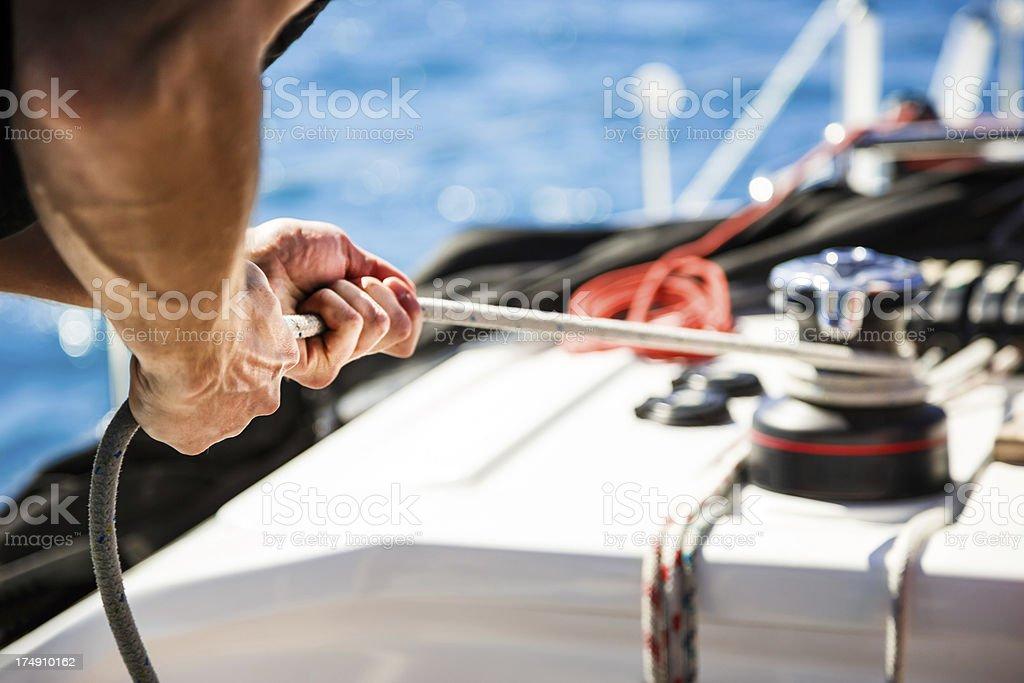 Sailing crew member pulling rope on sailboat - Royalty-free Adriatic Sea Stock Photo