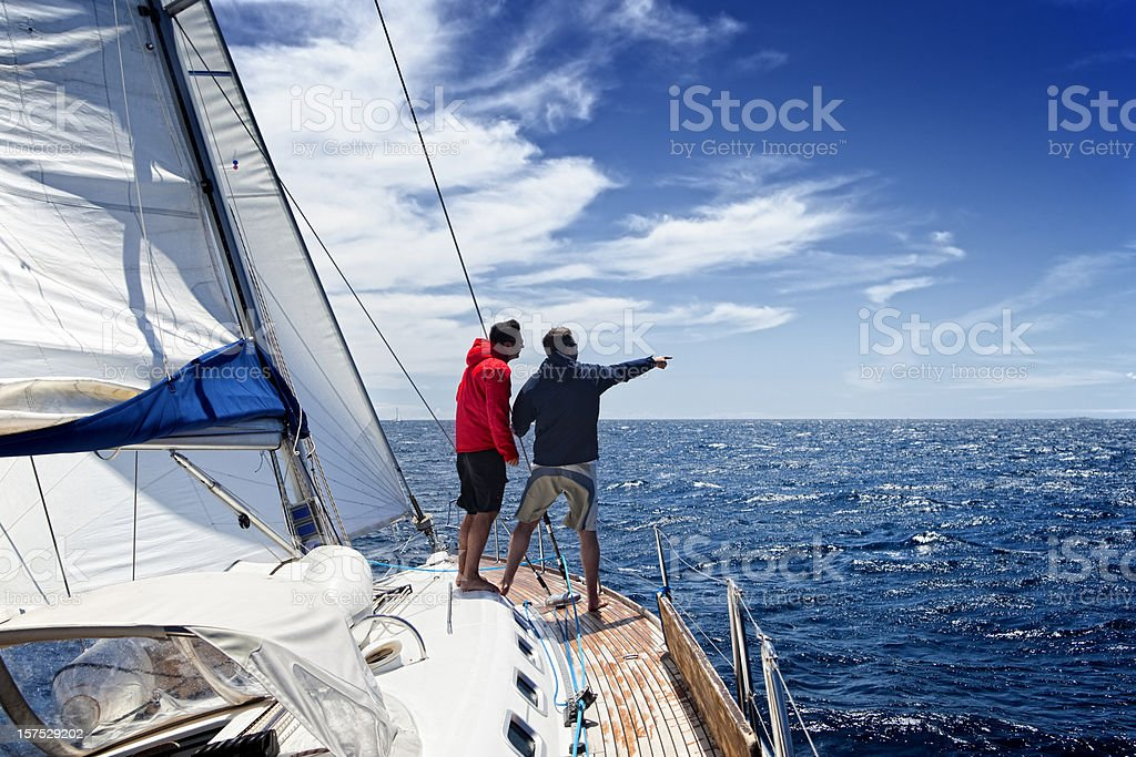 Sailing crew on sailboat observing the sea stock photo