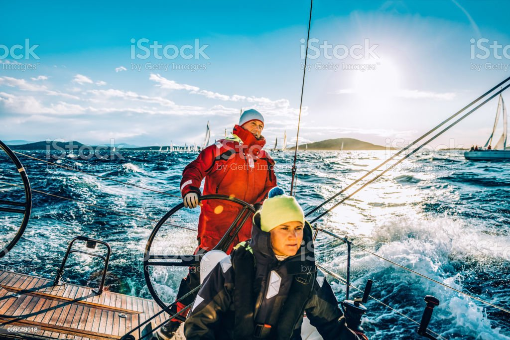 Sailing crew on sailboat on regatta on sunny autumn morning stock photo