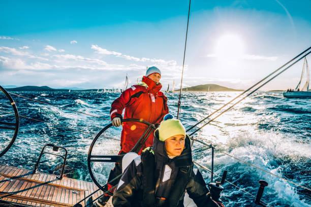 Vela a tripulação em veleiro na regata na ensolarada manhã de outono - foto de acervo