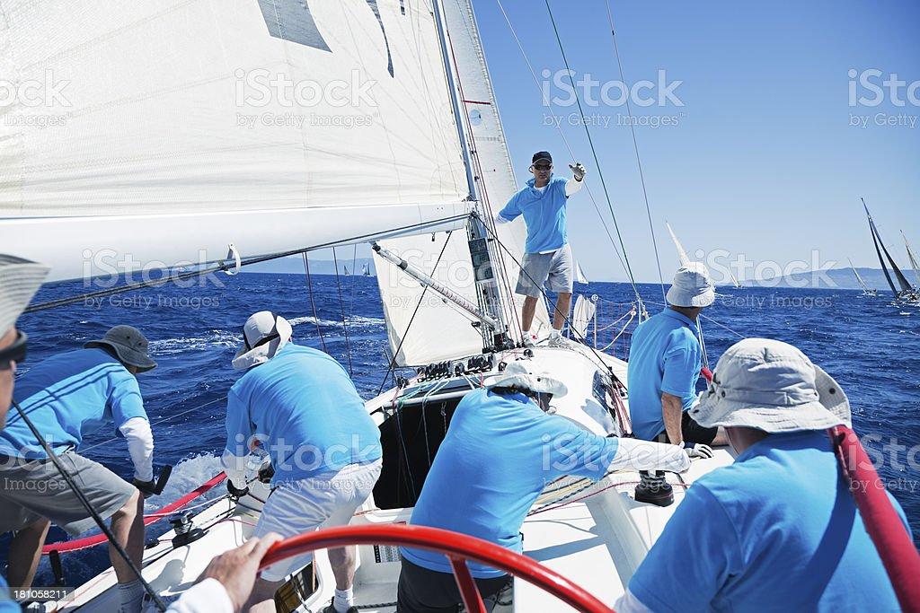 Sailing crew on sailboat stock photo