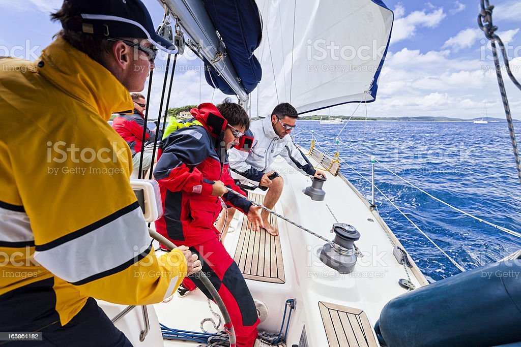 Sailing crew tacking a sailboat stock photo