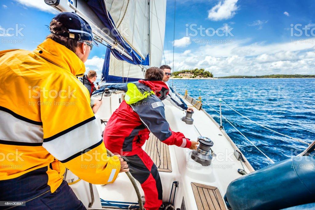 Sailing crew tacking a sailboat stock photo