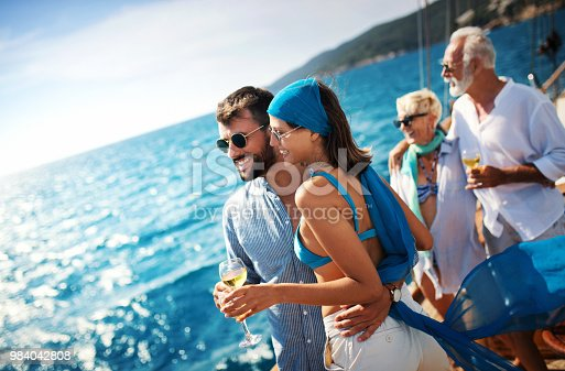 Closeup side view of mid 20's couple looking at sea and enjoying their sailing trip while sipping some sparkling white wine. There's mature couple in the background.