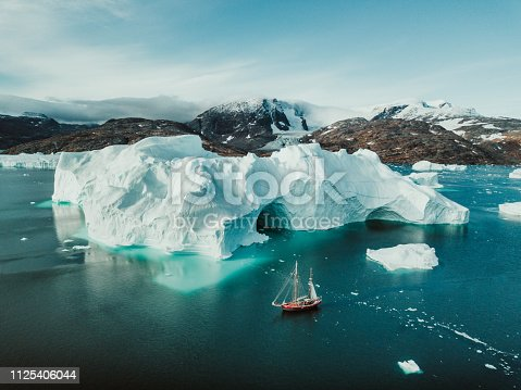 Photo from an expedition with a sailing boat through the beautiful vast landscape of huge icebergs and impressive mountainscapes in East Greenland.