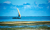 Lonely sailing fishing boat Dhow in the Indian ocean off the coast of Zanzibar