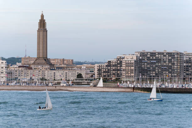 Sailing in Le Havre, France Two sailboats sail at sunset off the coast of Le Havre, France. On the left is St. Joseph's Church, built (like most of the city) after the destruction of WWII. le havre stock pictures, royalty-free photos & images