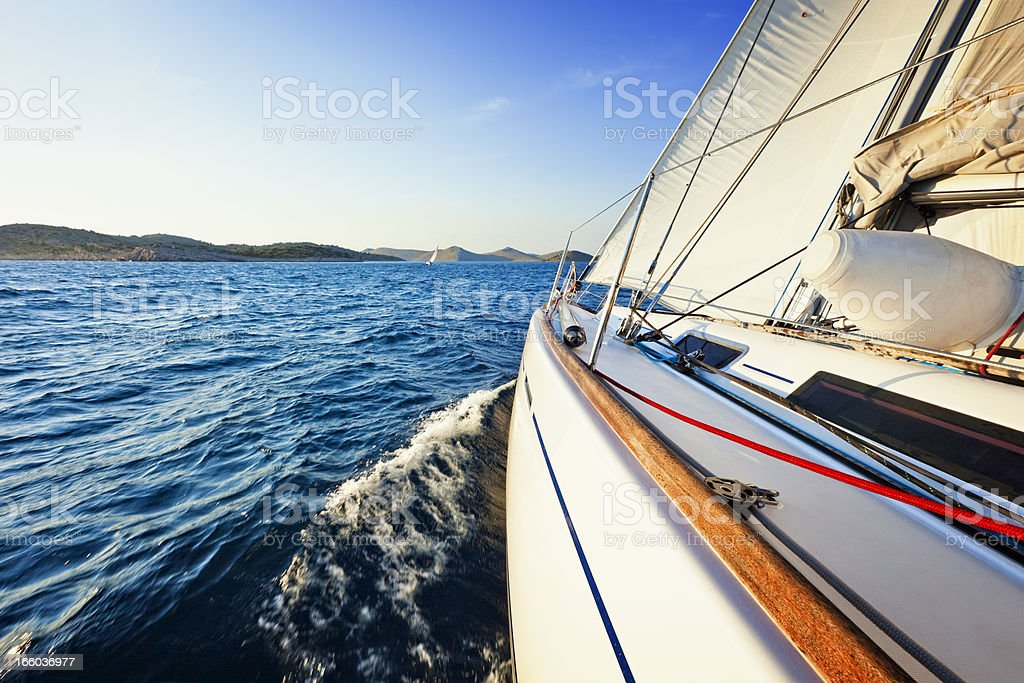 Sailing in the wind with sailboat at sunset royalty-free stock photo