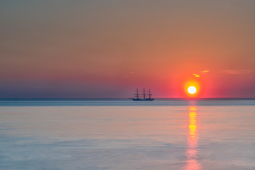A sailboat just of the coast with a colourful sunset behind it.