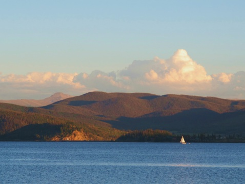 A lone sailboat navigates this beautiful mountain lake in the summertime- Granby, Colorado.