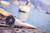 Compass lying on wooden dock pier in the foreground, sailing boats in the blurry background