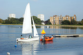 London, United Kingdom - October 4, 2015: People sail on the reservoir surrounded by the buildings in North London, England.